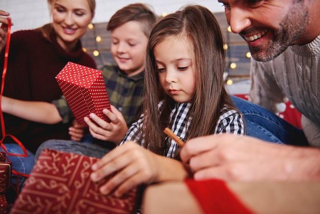 Schließen sie oben von der familie, die weihnachtsgeschenke im bett öffnet