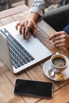 Schließen sie oben von der frau, die auf laptop in der kaffeestube schreibt