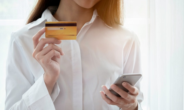 Schließen sie oben von der frau, die glücklich ist, kreditkarte und smartphone zu verwenden, um für on-line-kauf zu zahlen