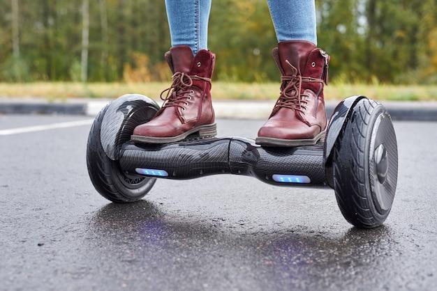 Schließen sie oben von der frau, die hoverboard auf asphaltstraße verwendet. füße auf elektroroller im freien