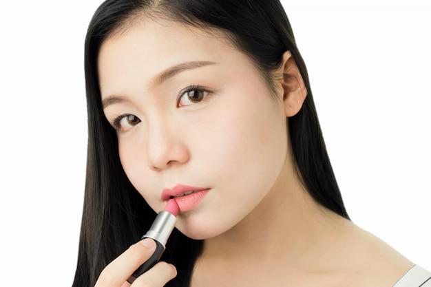 Schließen sie oben von der frau, die roten lippenstift mit bürste auf mundhautschönheit und -gesundheit anwendet.