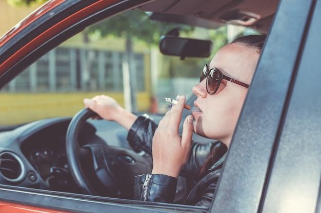 Schließen sie oben von der frau, die zigarette im auto raucht, während sie ein fahrzeug fahren, bedrohliches und gefährliches fahren