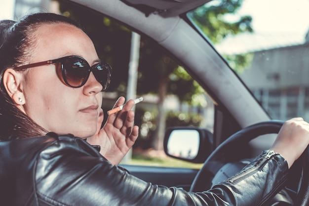 Schließen sie oben von der frau, die zigarette innerhalb des autos raucht, während sie ein fahrzeug fahren
