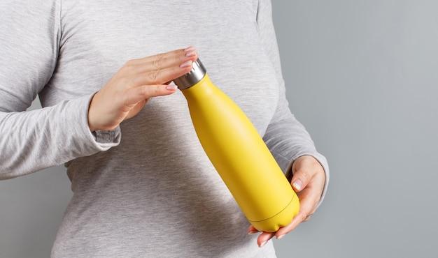 Schließen sie oben von der frau im grauen t-stück, das gelbe isolierte flasche auf grauem hintergrund hält