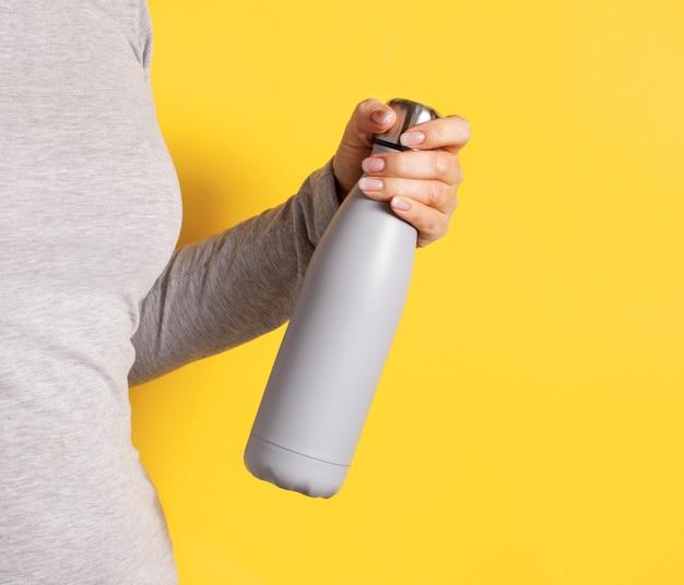 Schließen sie oben von der frau im grauen t-stück, das graue isolierte flasche auf gelbem hintergrund hält