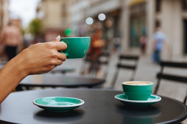 Schließen sie oben von der frauenhand, die hellblaue tasse heißen kaffees hält