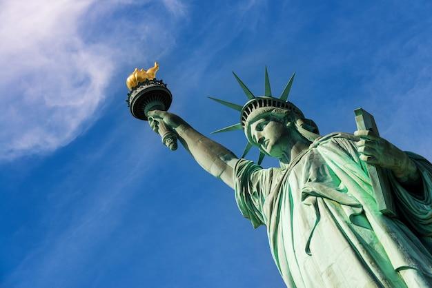 Schließen sie oben von der freiheitsstatue gegen einen bewölkten blauen himmel, new york city.