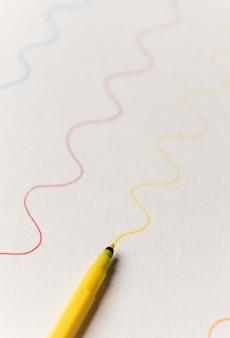 Schließen sie oben von der gelben textmarker-mallinie auf weißem papier