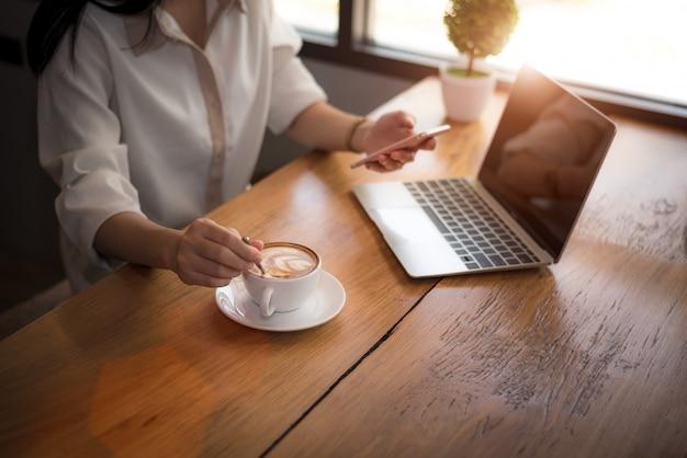 Schließen sie oben von der geschäftsfrau, die mit laptop arbeitet und kaffee im büro trinkt