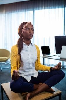 Schließen sie oben von der geschäftsfrau, die yoga tut