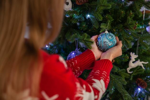 Schließen sie oben von der glücklichen frau, die weihnachtsbaum, konzept von neujahrsfeiertagen verziert