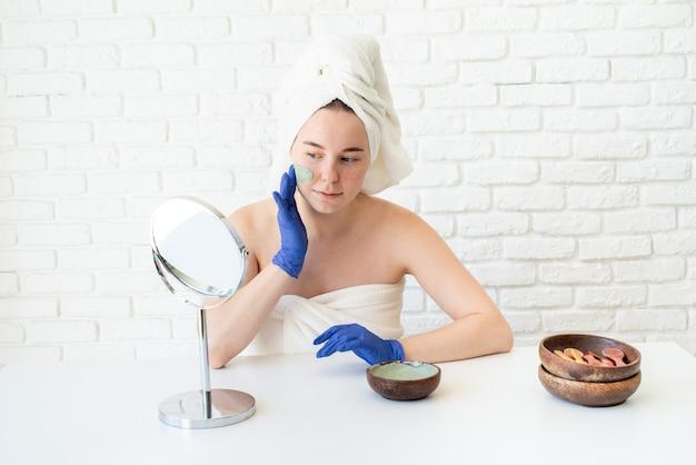 Schließen sie oben von der glücklichen jungen kaukasischen frau in den weißen badetüchern, die handschuhe tragen, die tongesichtsmaske anwenden, die den spiegel betrachten