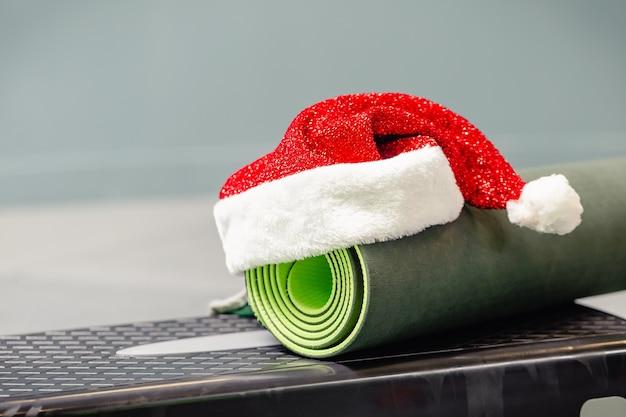 Schließen sie oben von der grauen matte mit weihnachtsmannmütze im fitnessstudio. bestes weihnachtsgeschenk für aktive person. yoga weihnachtskonzept.