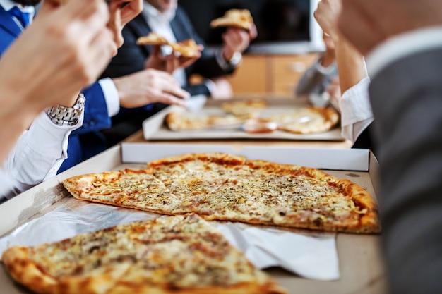 Schließen sie oben von der großen pizza im kasten auf tisch. geschäftsleute, die mittagspause haben.