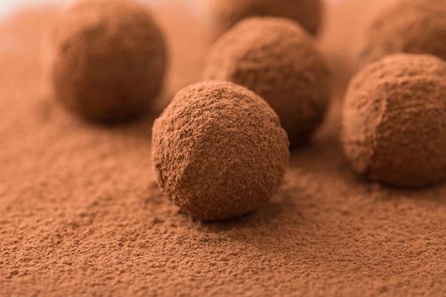 Schließen sie oben von der gruppe appetitanregenden trüffeln der schwarzen schokolade, die im kakaostaub bedeckt werden. geringe schärfentiefe.