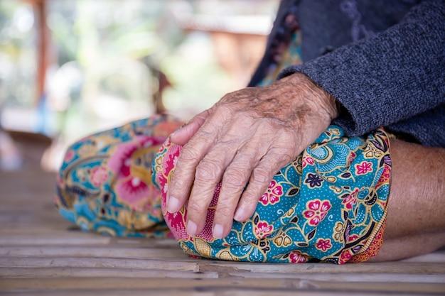 Schließen sie oben von der hand der älteren frau mit unscharfem hintergrund, asiatischen älteren leuten im ländlichen von asien