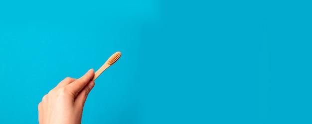 Schließen sie oben von der hand der frau, die bambuszahnbürste auf blauem hintergrund hält