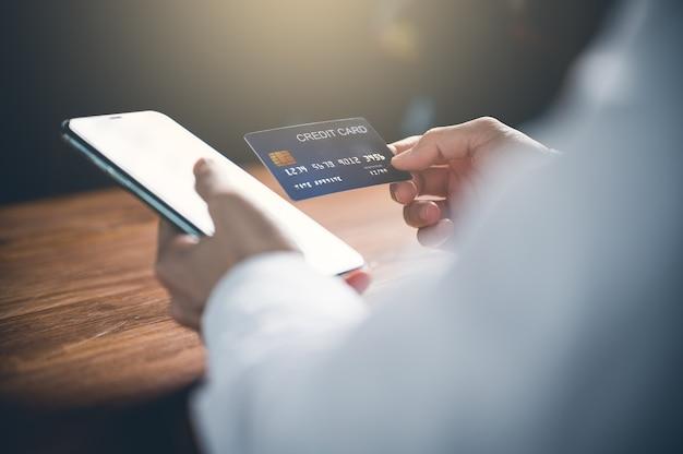 Schließen sie oben von der hand der frau, die handy oder handy für online-einkauf oder zahlung mit kreditkarte verwendet. online-shopping-konzept.