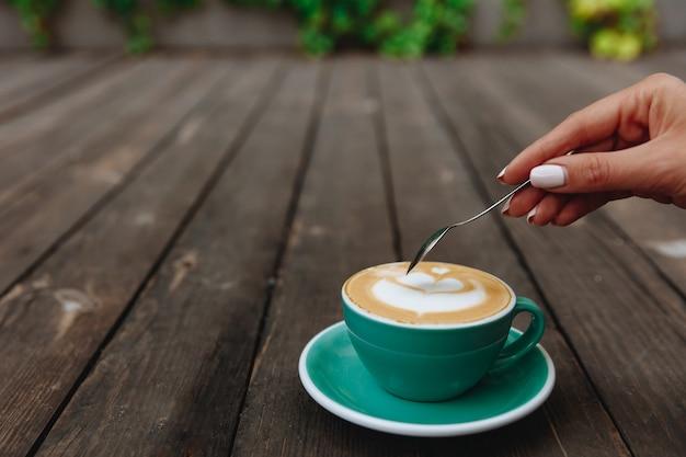 Schließen sie oben von der hand der frau, die ihren aroma-cappuccino rühren wird