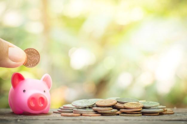 Schließen sie oben von der hand der frau, die münze in das rosa sparschwein für das speichern des konzeptes einsetzt