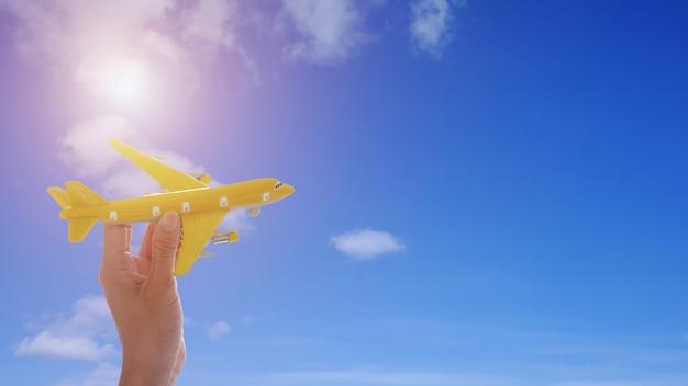 Schließen sie oben von der hand der frau, die spielzeugflugzeug auf hintergrund des blauen himmels mit sonnenschein hält.