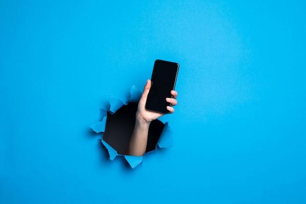 Schließen sie oben von der hand der frau, die telefon mit schrei für adv durch blaues loch in der papierwand hält.