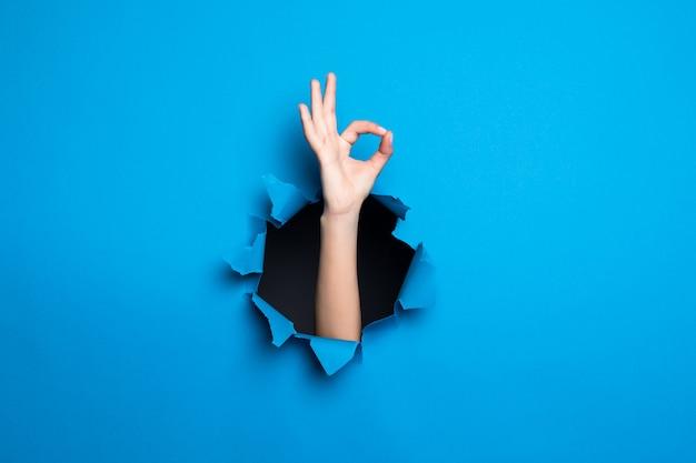 Schließen sie oben von der hand der frau mit der guten geste durch das blaue loch in der papierwand.