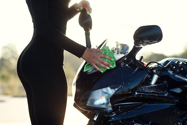 Schließen sie oben von der hand der verführerischen jungen frau, die stilvolles sportmotorrad wäscht und wischt es von rosa schaum bei sonnenaufgang ab.