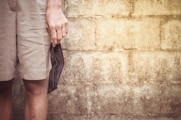 Schließen sie oben von der hand des mannes, die eine leere schwarze geldbörse hält