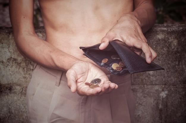 Schließen sie oben von der hand des mannes, die eine schwarze geldbörse und kleine münzen hält