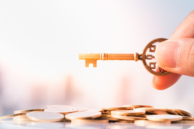 Schließen sie oben von der hand des mannes, die schlüssel auf stapel der münze mit stadtbild als hintergründen hält.
