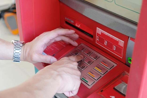 Schließen sie oben von der hand des mannes, die stift oder passwort auf atm-tastatur herein für transaktion einträgt