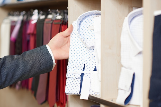 Schließen sie oben von der hand des mannes, die weißes hemd im blauen muster hält.