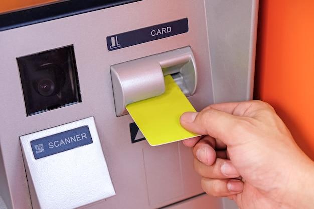 Schließen sie oben von der hand des mannes einstecken atm-karte in geldautomaten