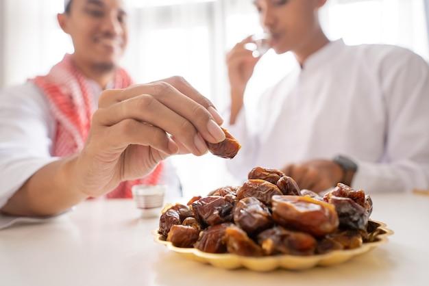 Schließen sie oben von der hand des muslims, die dattelfrucht nimmt, während sie zusammen während eines ramadan-festes zu hause iftar abendessen genießen
