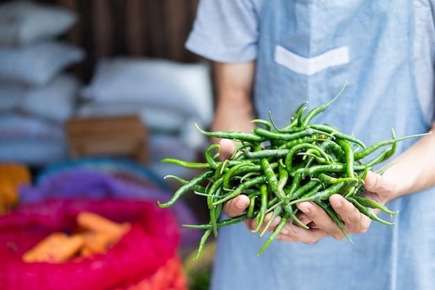 Schließen sie oben von der hand eines gemüsehändlers, der grüne chilis in einem gemüsestand hält