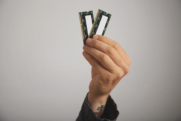 Schließen sie oben von der hand eines tätowierten mannes mit zwei ram-planken mit chips auf weißer wand