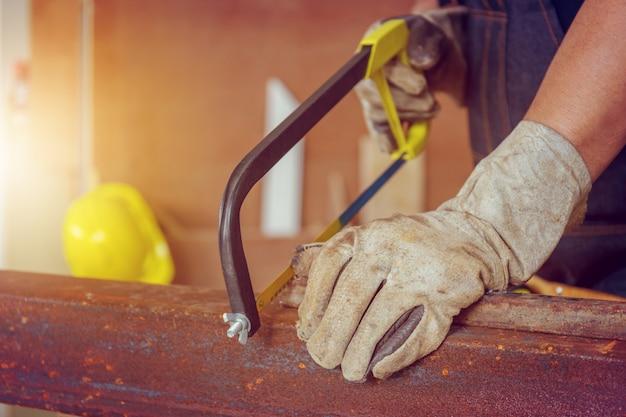 Schließen sie oben von der handwerkerarbeitskraft, die ein stahlrohr, technikerkonzept sägt.