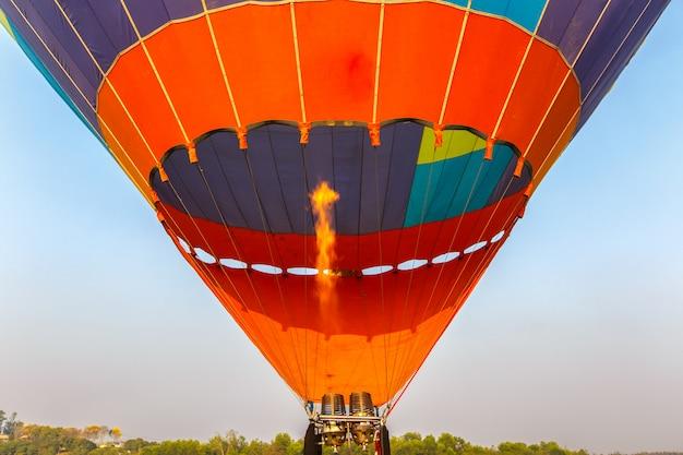 Schließen sie oben von der heißluftballon-brennerflamme, die zur sonnenuntergangzeit glüht.