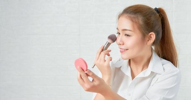 Schließen sie oben von der herrlichen bezaubernden schminke der asiatischen frau mit kosmetikprodukten.