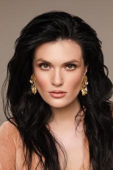 Schließen sie oben von der hübschen jungen frau mit make-up und stilvollen ohrringen, die kamera betrachten. modekonzept