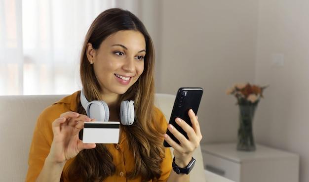 Schließen sie oben von der jungen frau, die kreditkarte hält und smartphone zu hause verwendet. online-shopping, geld ausgeben, lebenskonzepte genießen.