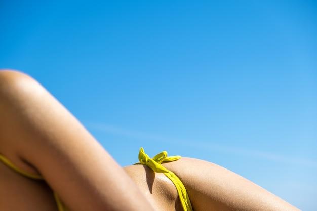 Schließen sie oben von der jungen frau hüfte und schulter, die auf strandkorb am seeufer-sonnenbad legen.