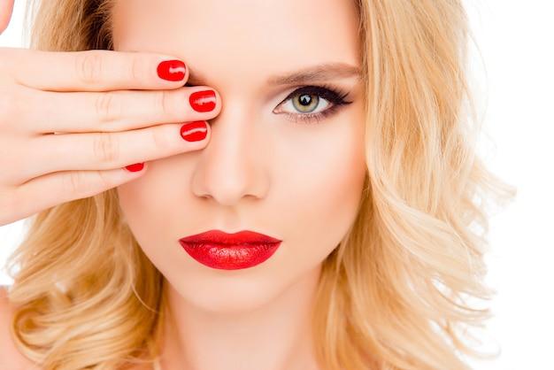 Schließen sie oben von der jungen frau mit hellem make-up, das auge hinter hand versteckt