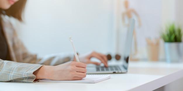 Schließen sie oben von der jungen geschäftsfrau, die auf laptop-computer schreibt