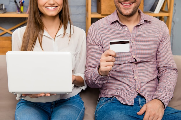 Schließen sie oben von der jungen glücklichen familie, die laptop und bankkarte hält