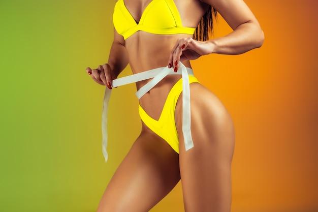 Schließen sie oben von der jungen passform und sportlichen frau mit vermesser in der stilvollen gelben badebekleidung auf gradientenwand perfekter körper bereit für sommerzeit