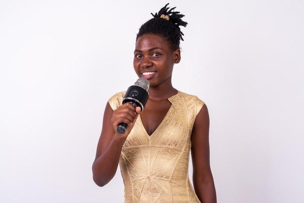 Schließen sie oben von der jungen schönen afrikanischen frau, die goldkleid bereit bereit hält, isoliert zu feiern