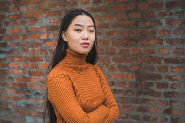 Schließen sie oben von der jungen schönen asiatischen frau, die zuversichtlich schaut und gegen backsteinmauer steht.