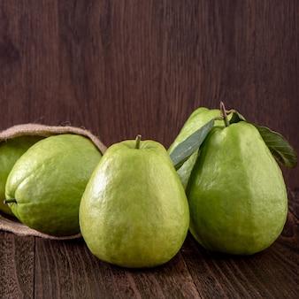 Schließen sie oben von der köstlichen schönen guave, die mit frischen grünen blättern lokalisiert auf dunklem holztischhintergrund gesetzt wird.